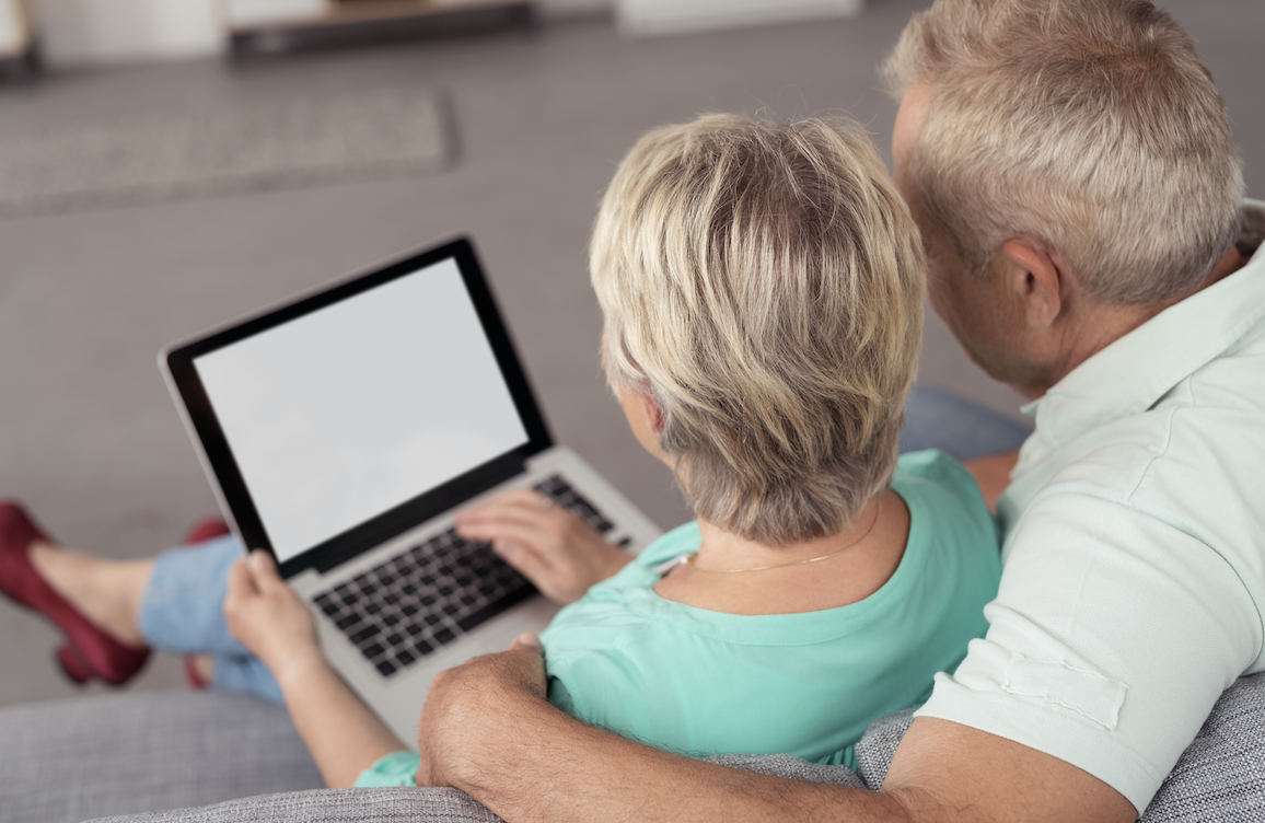 An older couple have a look at a property from home.