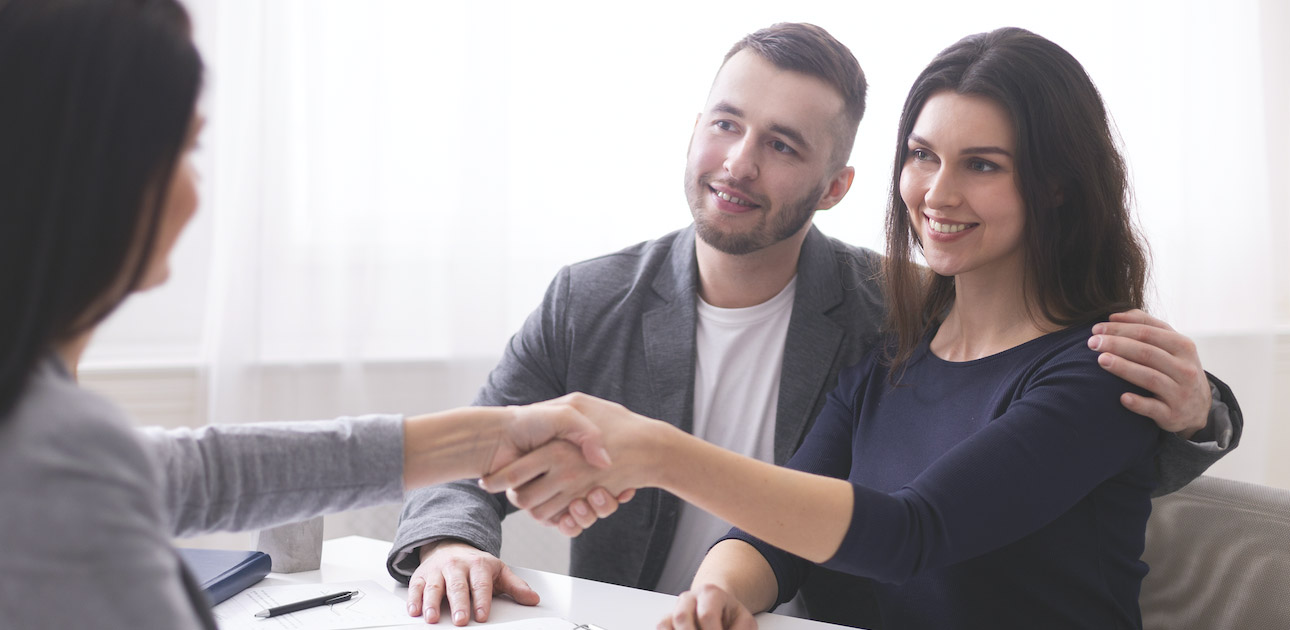 A happy couple shaking hands on a deal with a finance broker.