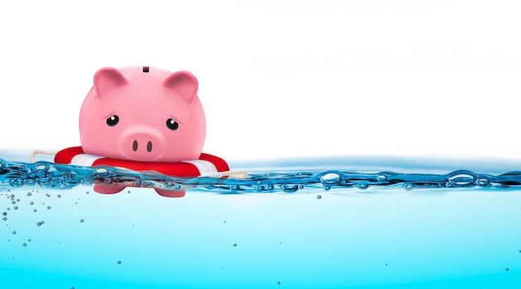 A piggly bank floating just staying above water.